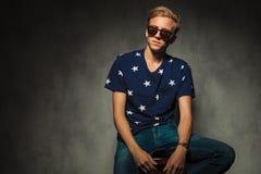 Blondes Mode-Modell mit den Gläsern, die auf einem Stuhl sitzen Lizenzfreie Stockfotos
