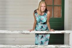 Blondes Mode-Modell wirft nahe Fensterläden geschlossenem Haus auf Stockbilder