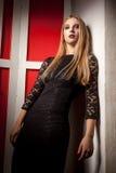 Blondes Modell, das in camera auf roter Weinlesewand schaut Lizenzfreie Stockfotos