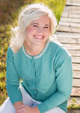 Blondes Modell, das draußen Porträt sitzt Lizenzfreies Stockbild