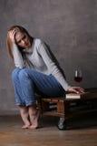 Blondes Modell, das ein Buch berührt Grauer Hintergrund Lizenzfreie Stockbilder