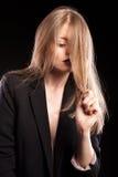 Blondes Modell, das in Mode Art auf schwarzem Hintergrund aufwirft Stockbild