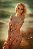 Blondes Modell der jungen Frau mit hellem Make-up draußen in der Modeart im Abendkleid hinter blauem Himmel Stockfotografie