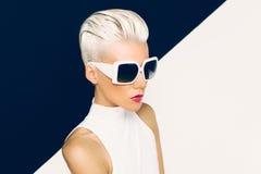 Blondes Modell in der modischen Sonnenbrille mit stilvollem Haarschnitt Art und Weise Stockfotografie
