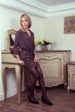 Blondes Modell der schönen jungen Mode, das nahe Secretaire aufwirft Stockfotos
