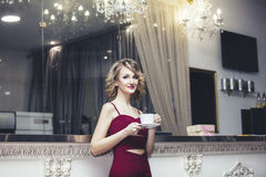 Blondes Modell der Schönheit in einem roten Overall elegant mit einem Cu Lizenzfreie Stockfotografie