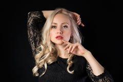 Blondes Modell in der Spitze auf dem schwarzen Hintergrund Lizenzfreies Stockbild