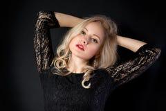 Blondes Modell in der Spitze mit den Händen über dem Kopf Stockbilder