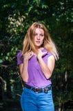 Blondes Modell des jungen schönen sexy Mädchens mit dem langen blonden Haar in den Jeans und in Jacke, die im Wald unter den Bäum Stockbild