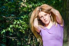 Blondes Modell des jungen schönen sexy Mädchens mit dem langen blonden Haar in den Jeans und in Jacke, die im Wald unter den Bäum Lizenzfreie Stockfotos