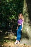 Blondes Modell des jungen schönen sexy Mädchens mit dem langen blonden Haar in den Jeans und in Jacke, die im Wald unter den Bäum Stockfotos
