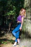 Blondes Modell des jungen schönen sexy Mädchens mit dem langen blonden Haar in den Jeans und in Jacke, die im Wald unter den Bäum Lizenzfreies Stockbild