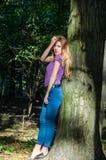 Blondes Modell des jungen schönen sexy Mädchens mit dem langen blonden Haar in den Jeans und in Jacke, die im Wald unter den Bäum Lizenzfreie Stockfotografie