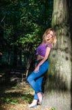 Blondes Modell des jungen schönen sexy Mädchens mit dem langen blonden Haar in den Jeans und in Jacke, die im Wald unter den Bäum Stockfotografie