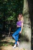 Blondes Modell des jungen schönen sexy Mädchens mit dem langen blonden Haar in den Jeans und in Jacke, die im Wald unter den Bäum Stockbilder