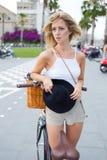 Blondes Modell des Zaubers mit einer schönen Zahl, die mit ihrem Weinlesefahrrad aufwirft Stockfoto