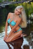 Blondes Modell des Zaubers mit sexy Körper im blauen Bikini, der recht am Naturstandort aufwirft Stockfoto