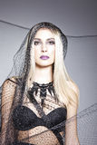 Blondes Modell im Schwarzen mit einem Schleier auf ihrem Kopf Stockfotografie