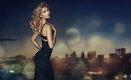 Blondes Modell mit dem langen Haar, das im schwarzen Kleid aufwirft Stockbild