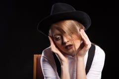 Blondes Modell mit den Hosenträgern und weißem Hemd, die einen Hut tragen Stockbilder