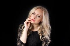 Blondes Modell mit der Hand nahe ihren Lippen Lizenzfreie Stockfotos