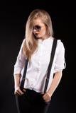 Blondes Modell mit Hosenträgern und weißem Hemd Stockfotografie