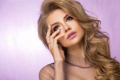 Blondes Modemädchen mit dem langen und glänzenden gelockten Haar Lizenzfreie Stockfotos