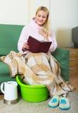 Blondes nehmendes Fußbad zu Hause Stockfoto