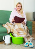 Blondes nehmendes Fußbad zu Hause Stockbilder