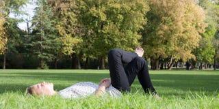 Blondes nettes Lügen auf grünem Gras Lizenzfreie Stockfotos