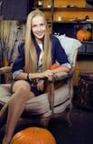 Blondes nettes Mädchen in Halloween-Innenraum mit Kürbis Stockfotos