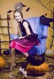 Blondes nettes Mädchen in Halloween-Innenraum mit Kürbis Lizenzfreie Stockfotografie