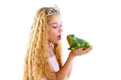 Blondes Prinzessinmädchen, das eine Froschgrünkröte küsst Stockfotos