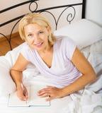 Blondes reifes Frauenschreiben im Tagebuch Lizenzfreie Stockfotografie