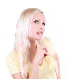Blondes reizvolles Mädchen, das, getrennt auf Weiß denkt Lizenzfreie Stockfotos