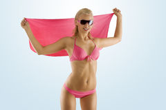 Blondes reizvolles Mädchen im rosafarbenen Bikini und in den Sonnenbrillen Stockfotografie