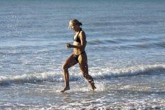 Blondes reizvolles Mädchen laufen in den Ozean stockbilder