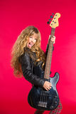 Blondes Rock-and-Rollmädchen mit Bass-Gitarre auf Rot Lizenzfreie Stockfotos