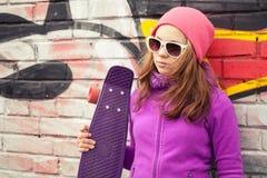 Blondes schönes Jugendlichegriffskateboard Stockfoto