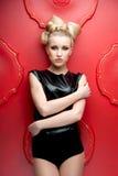 Blondes schönes junges Mädchen auf rotem Hintergrund Lizenzfreies Stockbild
