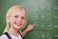 Blondes Schulmädchen, das auf etwas zeigt Lizenzfreie Stockfotos