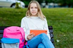 Blondes Schulmädchen des kleinen Mädchens Sommer in der Natur Sitzt auf Bank in den Händen, die eine Tablette halten Nach Klassen Stockbilder