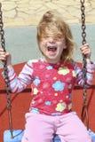 Blondes schwingunordentliches Haar des parks des kleinen Mädchens Stockfotos