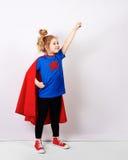 Blondes Sechsjahresmädchen kleidete wie der Superheld an, der Spaß zu Hause hat Weiße Wand auf Hintergrund Stockfotografie