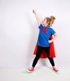 Blondes Sechsjahresmädchen kleidete wie der Superheld an, der Spaß zu Hause hat Weiße Wand auf Hintergrund Lizenzfreie Stockfotos