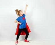 Blondes Sechsjahresmädchen kleidete wie der Superheld an, der Spaß zu Hause hat Weiße Wand auf Hintergrund Stockbilder
