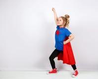 Blondes Sechsjahresmädchen kleidete wie der Superheld an, der Spaß zu Hause hat Weiße Wand auf Hintergrund Stockfoto