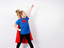 Blondes Sechsjahresmädchen kleidete wie der Superheld an, der Spaß zu Hause hat Weiße Wand auf Hintergrund Lizenzfreie Stockfotografie
