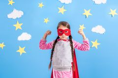 Blondes Sechsjahresmädchen kleidete wie der Superheld an, der Spaß zu Hause hat Scherzen Sie auf dem Hintergrund der hellen blaue Lizenzfreie Stockfotografie