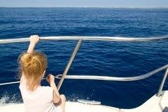 Blondes Segeln der hinteren Ansicht des kleinen Mädchens im Boot Stockbilder